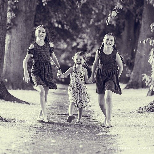 Three girls holding hands and running with Robert Nelson Family Photographer